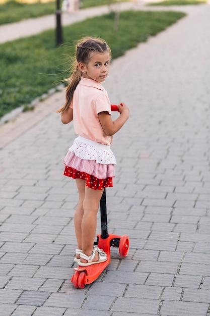 Portrait, girl, debout, rouges, pousser, scooter, regarder appareil-photo Photo gratuit