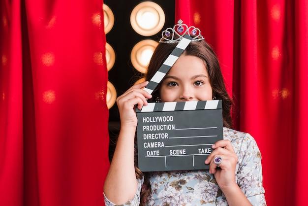 Portrait, girl, porter, couronne, tenue, clapper, devant, elle, visage Photo gratuit