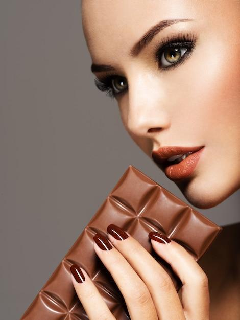 Portrait De Glamour Belle Femme Aux Ongles Bruns Tient Une Barre De Chocolat Photo gratuit