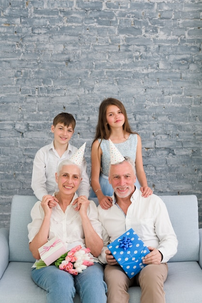 Portrait de grands-parents heureux portant un chapeau de fête avec leurs petits-enfants Photo gratuit