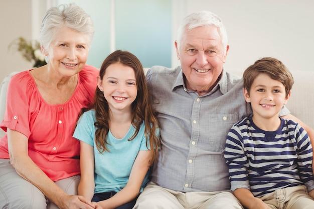 Portrait de grands-parents et petits-enfants assis sur un canapé dans le salon Photo Premium