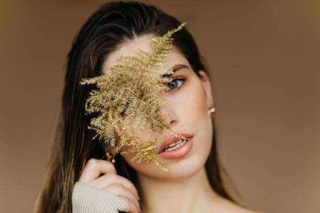 Portrait En Gros Plan D'une Fille Blanche Fascinante Avec Plante. Femme Calme Inspirée Debout Sur Un Mur Marron. Photo gratuit