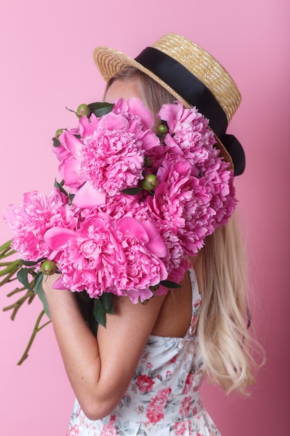 Portrait De Gros Plan De Jeune Femme En Robe D'été Et Chapeau De Paille Tenant Un Bouquet De Pivoines Sur Son épaule Photo Premium