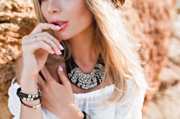 Portrait De Gros Plan De Jolie Fille Blonde Aux Cheveux Longs Sur Fond De Roche. Elle Garde Le Doigt Sur Les Lèvres. Photo gratuit