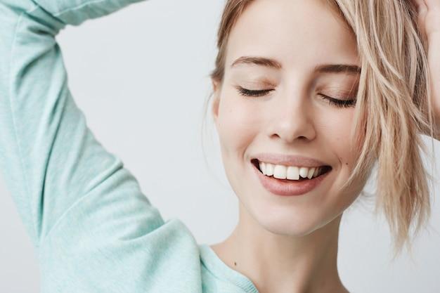 Portrait En Gros Plan D'une Magnifique Femme Blonde Joyeuse Avec Des Traits Tendres, Pose Contre Le Mur Gris, Sourit Brodly, Montre Des Dents Blanches Et Une Peau Pure Parfaite. Belle Femme Aux Yeux Fermés Photo gratuit