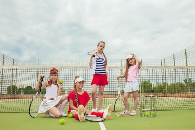 Portrait De Groupe De Filles En Tant Que Joueurs De Tennis Tenant Une Raquette De Tennis Contre L'herbe Verte De La Cour Extérieure Photo gratuit