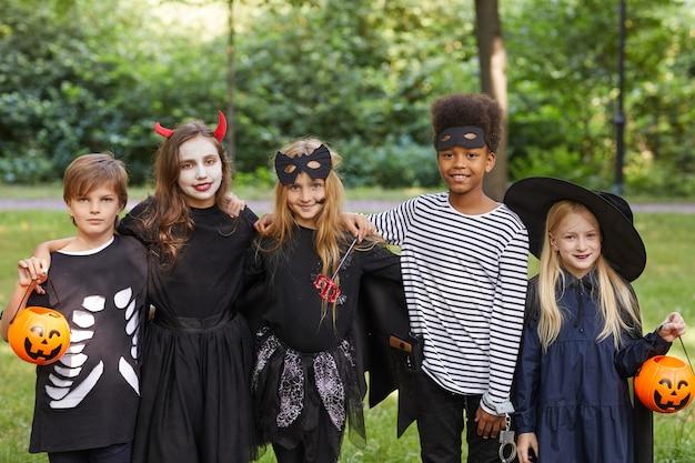 Portrait De Groupe Multiethnique D'enfants Portant Des Costumes D'halloween En Se Tenant Debout à L'extérieur Et Photo Premium