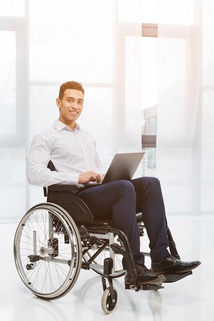 Portrait, de, a, handicapé, sourire, jeune homme affaires, s'asseoir fauteuil roulant, utilisation, ordinateur portable, dans, les, bureau Photo gratuit