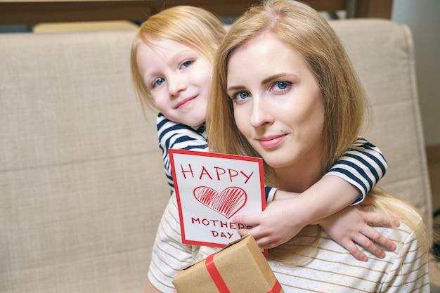 Portrait D'une Heureuse Mère Et Fille étreignant Et Tenant Une Carte Et Un Cadeau à La Maison. Concept De La Fête Des Mères. Photo Premium