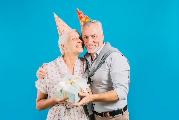 Portrait de l'heureux couple de personnes âgées tenant un cadeau d'anniversaire sur fond bleu Photo gratuit