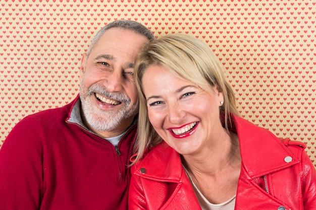 Portrait heureux du couple de personnes âgées contre le papier peint en forme de cœur Photo gratuit