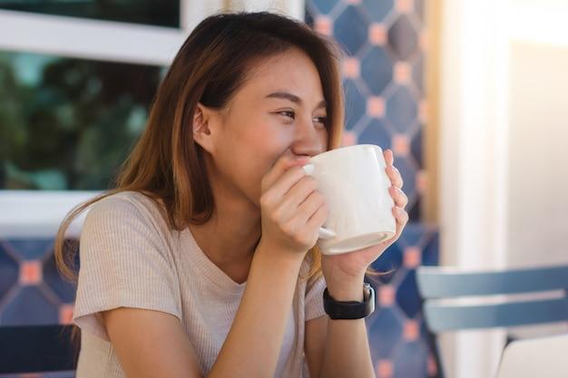 Portrait, heureux, jeune, asiatique, femme affaires, à, tasse à mains, boire café, matin Photo gratuit