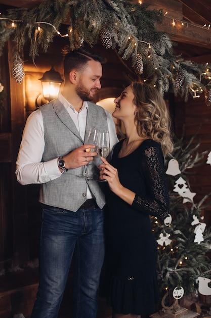 Portrait De L'heureux Jeune Couple Dans Des Tenues élégantes Souriant Face à Face Avec Deux Verres De Champagne Photo gratuit