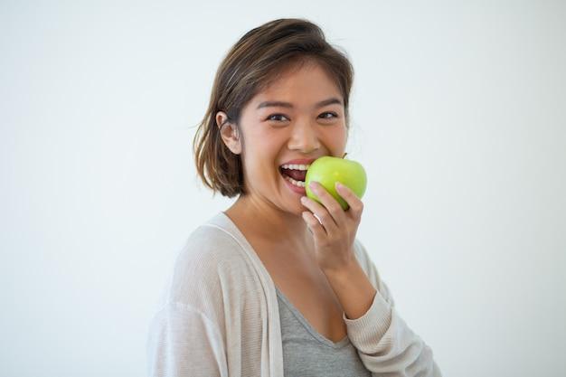 Portrait, heureux, jeune femme, mordre pomme Photo gratuit