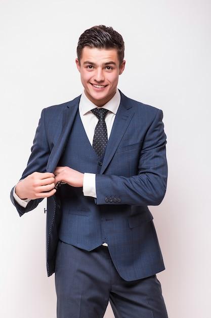 Portrait D'heureux Jeune Homme D'affaires Souriant En Costume Bleu Isolé Sur Mur Blanc Photo gratuit