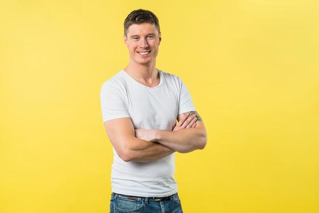 Portrait, heureux, jeune homme, à, bras croisés, regarder, debout, caméra, contre, jaune, toile de fond Photo gratuit