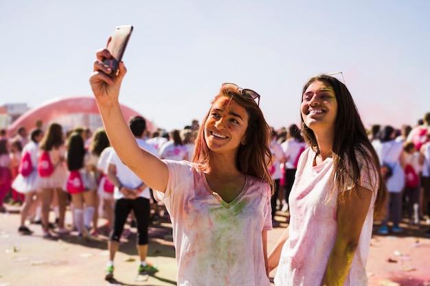 Portrait, de, une, heureux, jeunes femmes, prenant, selfie, sur, téléphone portable, pendant, holi, festival Photo gratuit