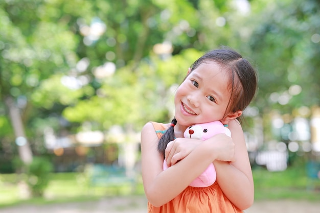 Portrait De L'heureux Petit Enfant Asiatique Dans Un Jardin Verdoyant Avec étreindre L'ours En Peluche Et Regarder La Caméra. Photo Premium