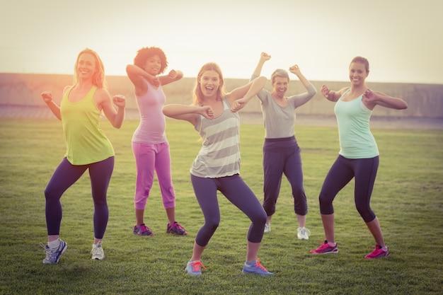 Portrait, de, heureux, sportif, femmes, danse, pendant, cours de conditionnement physique, dans, parc Photo Premium