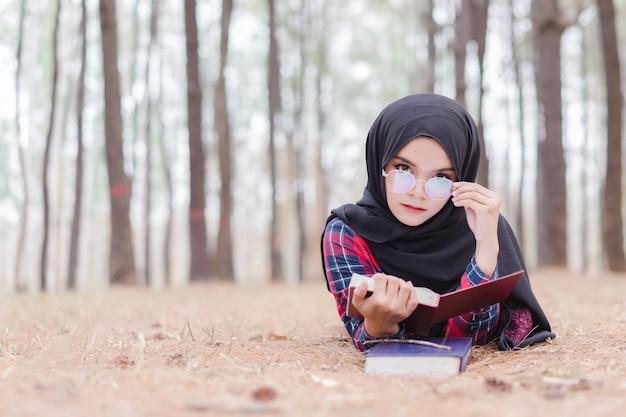 Portrait de hijab noir de jeune femme musulmane heureuse et chemise écossaise, lisant un livre en automne. Photo Premium