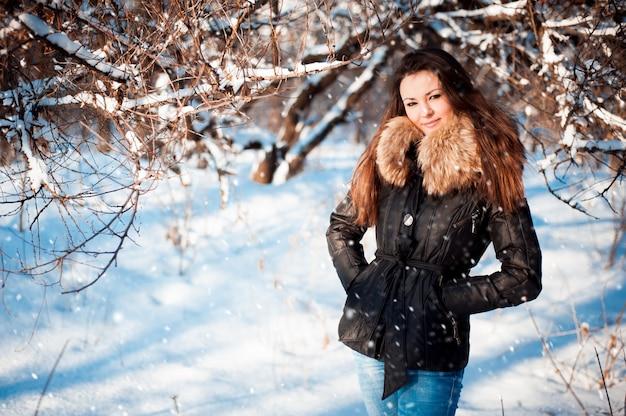 Portrait d'hiver d'une jeune fille dans une veste avec un col en fourrure. Photo Premium