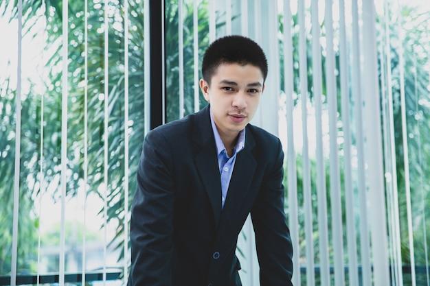 Portrait d'homme d'affaires asiatique avec son travail au bureau Photo Premium