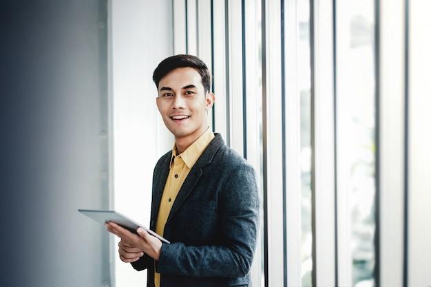 Portrait d'un homme d'affaires heureux, debout près de la fenêtre du bureau Photo Premium