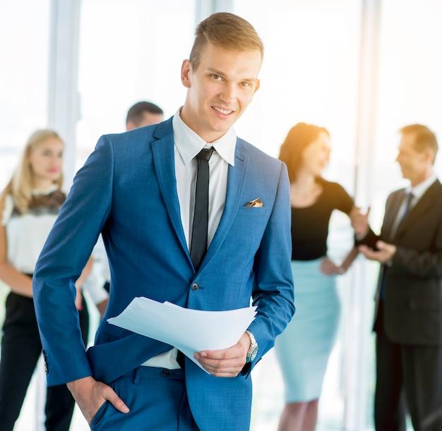 Portrait d'un homme d'affaires heureux munis de documents avec des collègues en arrière-plan Photo gratuit