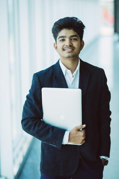 Portrait D'homme D'affaires Indien Heureux à L'aide D'un Ordinateur Portable Au Bureau Photo gratuit