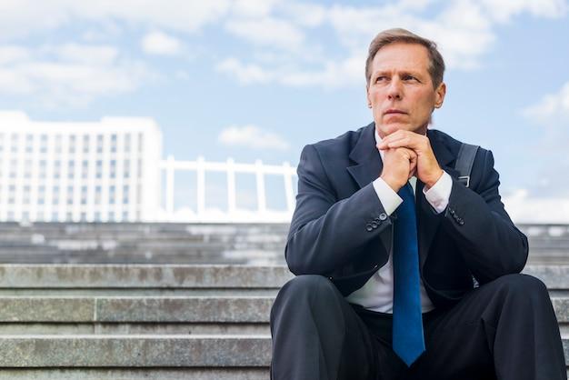 Portrait d'un homme d'affaires mature assis sur un escalier Photo gratuit