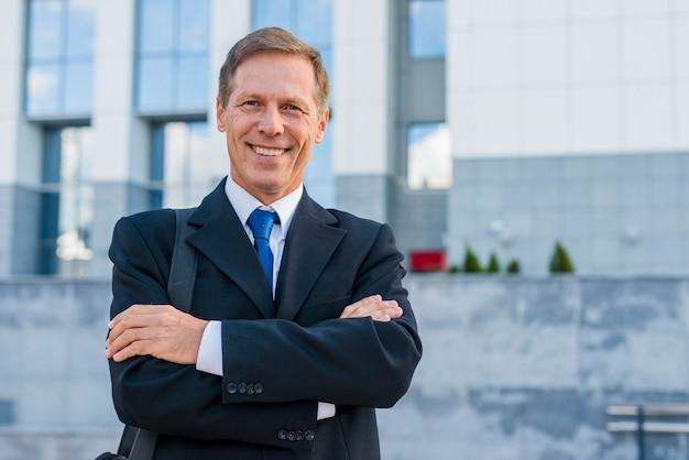Portrait d'un homme d'affaires mature heureux avec les bras croisés Photo gratuit