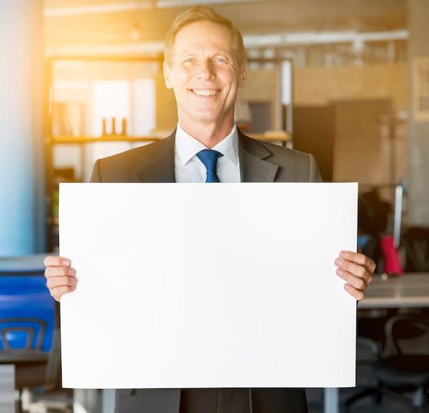 Portrait d'un homme d'affaires mature souriant tenant une pancarte blanche Photo gratuit