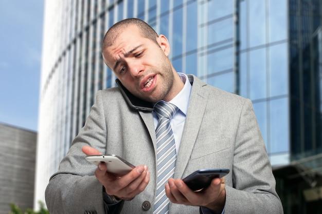 Portrait d'un homme d'affaires occupé en utilisant trois téléphones à la fois Photo Premium