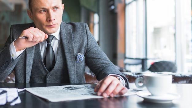 Portrait d'un homme d'affaires sérieux avec un journal en détournant les yeux Photo gratuit