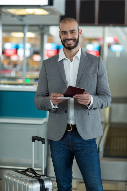 Portrait D'homme D'affaires Souriant Avec Des Bagages Vérifiant Sa Carte D'embarquement Photo gratuit
