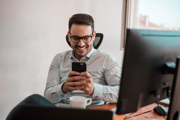 Portrait d'un homme d'affaires souriant heureux à lunettes à l'aide de smartphone tout en étant assis au bureau. Photo Premium