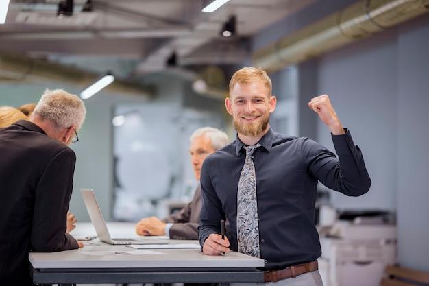 Portrait d'homme d'affaires souriant, serrant son poing, tandis que l'équipe discute en arrière-plan Photo gratuit