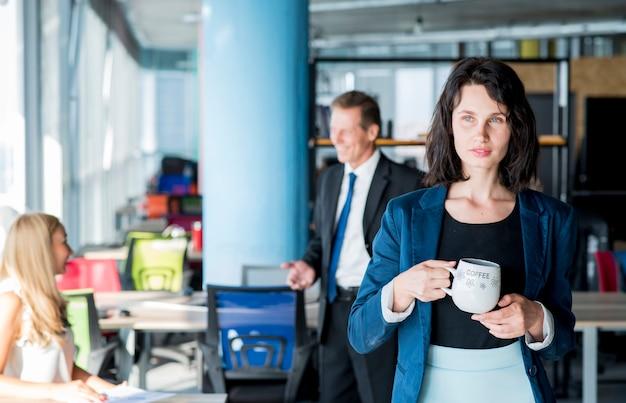 Portrait d'un homme d'affaires tenant une tasse de café au bureau Photo gratuit