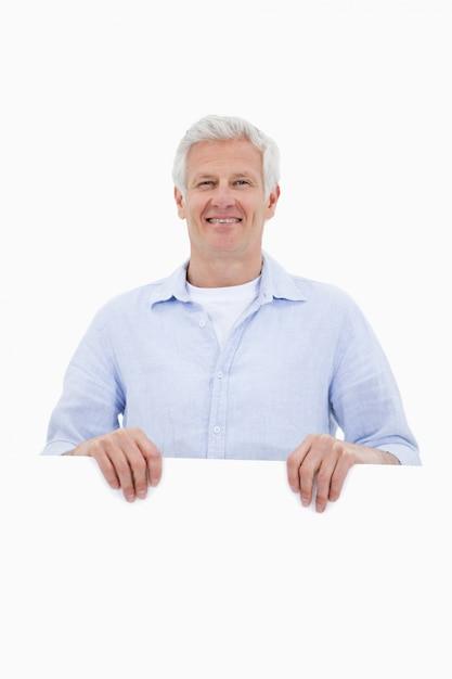 Portrait d'un homme d'âge mûr debout derrière un panneau vierge Photo Premium