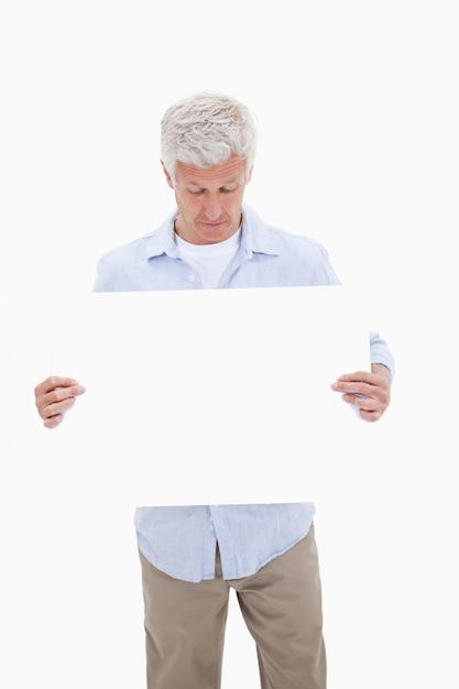 Portrait d'un homme d'âge mûr en regardant un panneau vierge Photo Premium