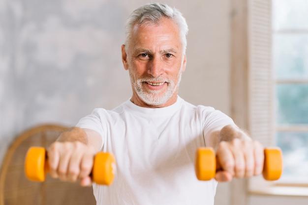 Portrait d'un homme âgé souriant tenant des haltères Photo gratuit
