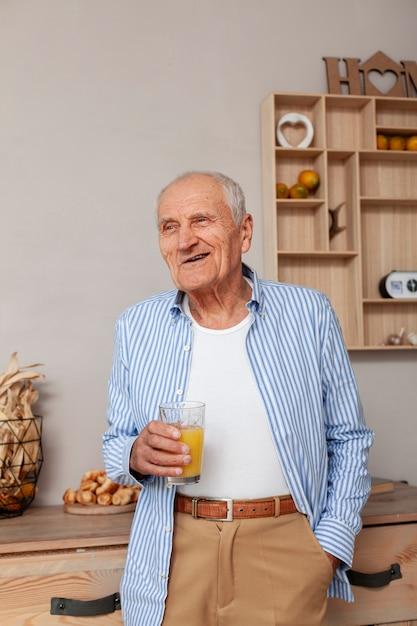 Portrait D'un Homme âgé Tenant Un Verre De Jus Photo gratuit