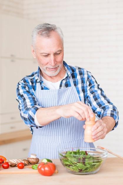 Portrait, de, a, homme aîné, ajouter, poivre, à, moulin, dans, saladier vert, sur, table bois Photo gratuit