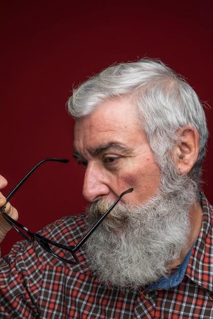Portrait, De, A, Homme Aîné, Tenant Lunettes, Dans, Main, Debout, Contre, Toile De Fond Couleur Photo gratuit