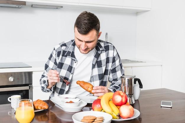Portrait, homme, apprécier, croissant, cuisine Photo gratuit