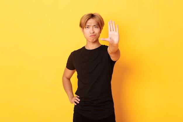 Portrait D'un Homme Asiatique Sérieux Déçu, Souriant Mécontent Et étendre La Main, Montrant Le Geste D'arrêt, Mur Jaune Photo gratuit