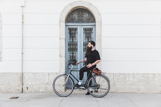 Portrait d'un homme assis sur un vélo devant la porte bleue Photo gratuit