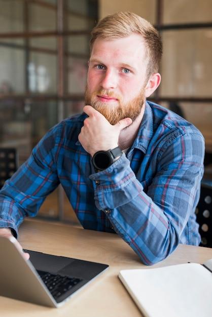 Portrait d'homme barbu assis devant un ordinateur portable sur le lieu de travail Photo gratuit
