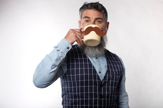 Portrait d'homme barbu buvant dans une tasse avec une fausse moustache en papier Photo Premium