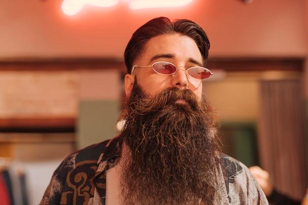 Portrait d'un homme barbu portant des lunettes de soleil dans le magasin Photo gratuit